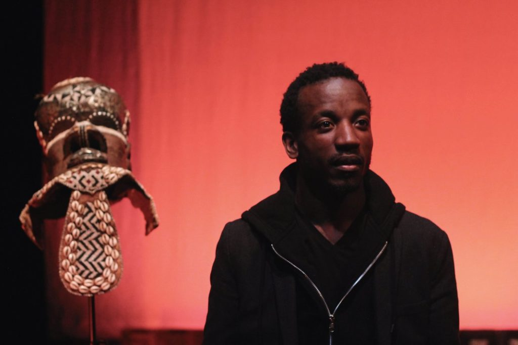 A young man in a black hoodie. Next to him is an African mask.
