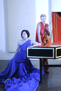Asako Hirabayashi and Margaret Humphrey, with harpsichord and violin, wearing elaborate cerulean blue gown & red gown