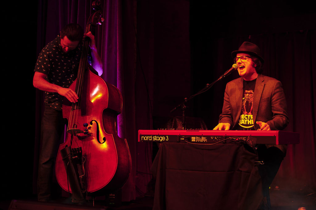 Man in black fedora playing a red electric keyboard, a man at his side plays upright base.