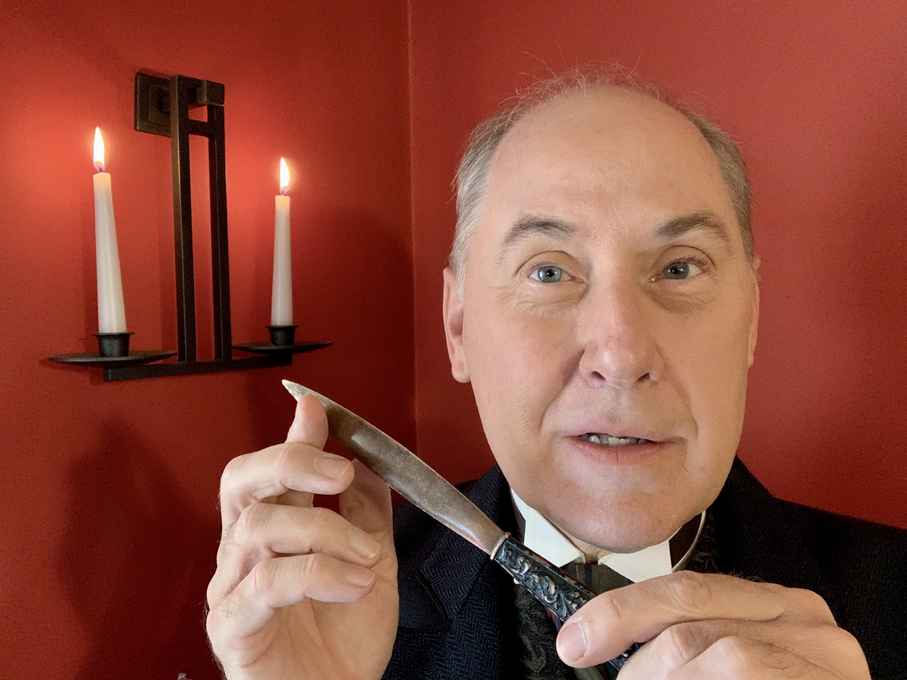 A man holds a knife in front of a red background with two white burning candles