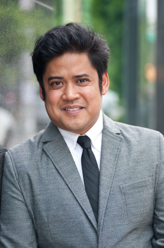 Park Square Theatre's Artistic Director Flordelino Lagundino — head and torso shot, wearing grey jacket, white shirt, and black necktie