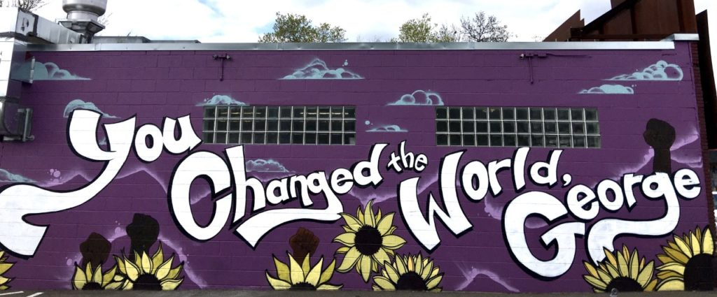 """Photo of a mural - a purple wall with paintings of raised fists and the words, """"You Changed the World, George!"""""""