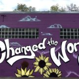 "Photo of a mural - a purple wall with paintings of raised fists and the words, ""You Changed the World, George!"""