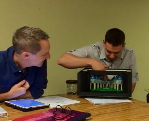 Scenic Designer Eli Schlatter (right) shows Director Doug Scholz-Carlson (left) his color set design model