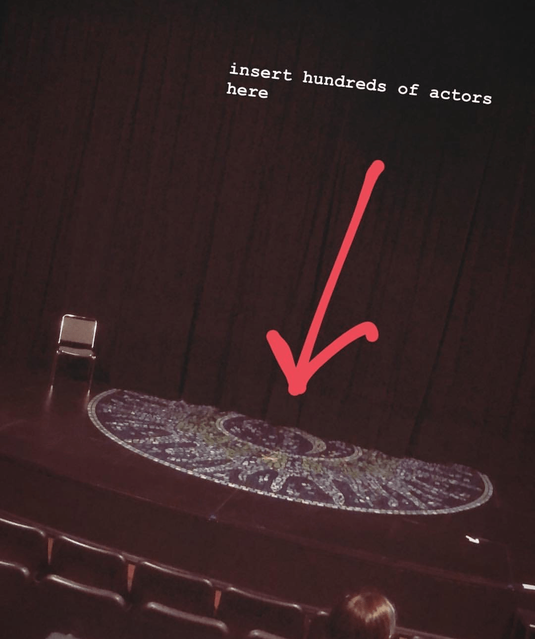 "Picture of Stage with an arrow pointing to center stage with text saying ""insert hundreds of actors here."""