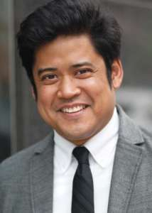 Head and shoulders photo of Lagundino Flordelino, outdoors, wearing grey jacket, white shirt, and black necktie