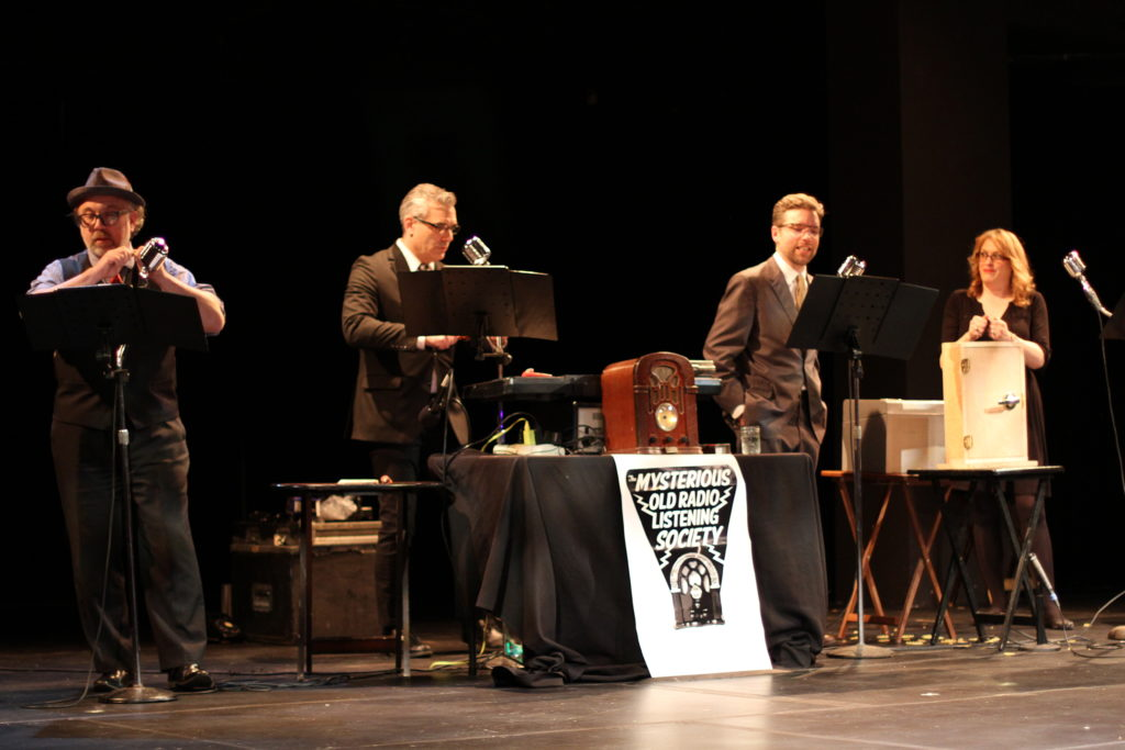 Four radio actors on stage with old-timey microphones and sound effects equipment.