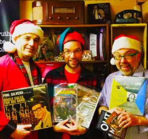 Three white men in Santa hats and Christmas sweaters holding vintage records.