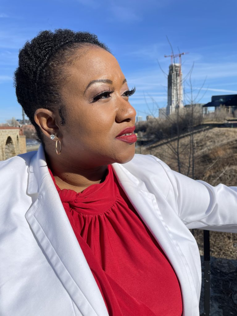 A woman in red bluse and white blazer calmly looks into the distance. An industrial scene in the background