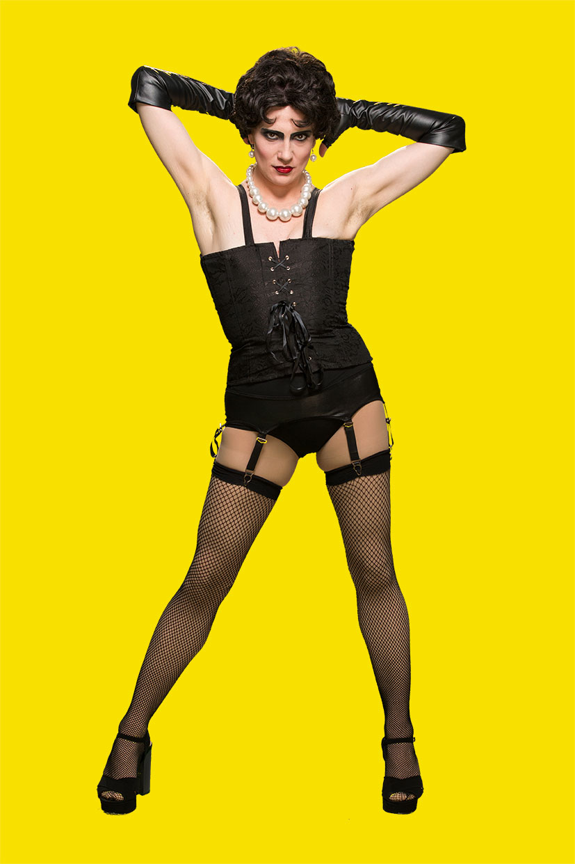 Photo of an androgynous actor in black corset, gloves, and fishnet tights.