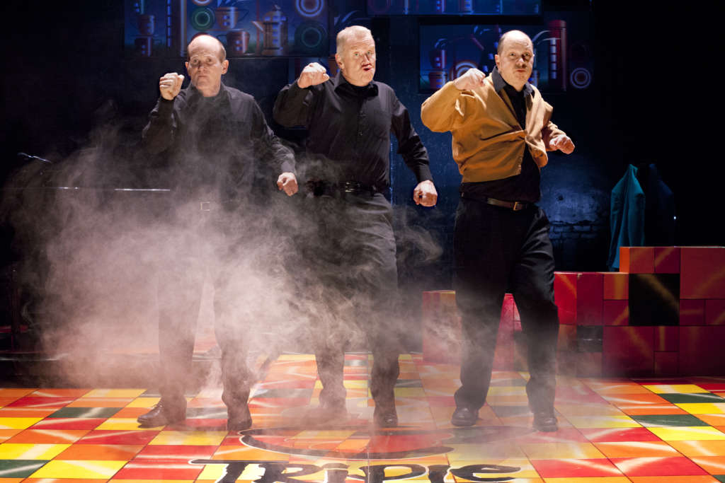 3 male cast members in dark clothing in cloud of stage smoke