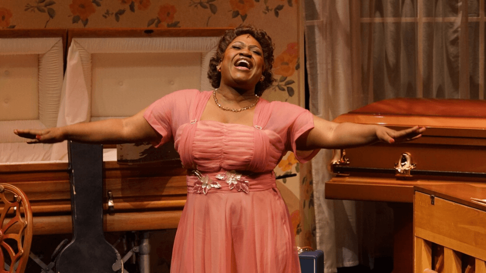 Rosetta singing with her arms outstretched, in front of a casket, wearing rose colored dress