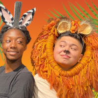 Two young people, one is wearing zebra ears and the other a lion's mane.