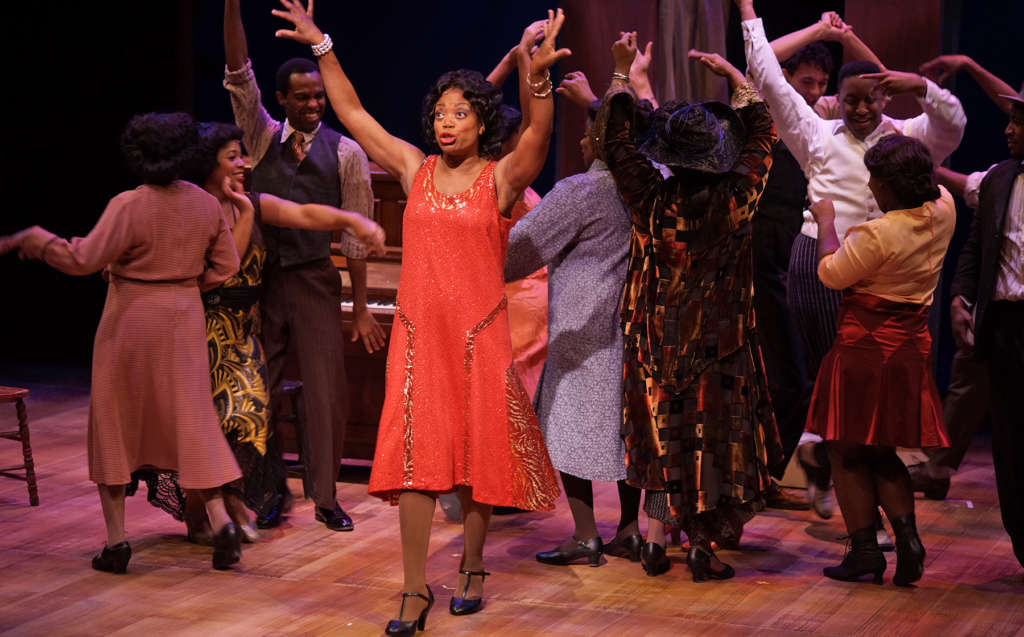 "Dance scene ""Push Da Button"" from The Color Purple in which the main actor in front is African American woman wearing a bright read dress in 1940s style, surrounded by a group of other dancers"