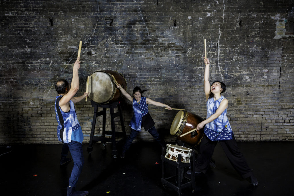 Three drummers in blue tunics with drumsticks in the air surround three drumbs