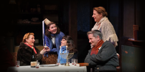 Five characters from the Diary of Anne Frank gathered around a table with a menorah