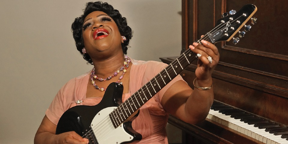 Rosetta singing and playing an electric guitar, sitting in front of an upright piano, wearing rose colored dress