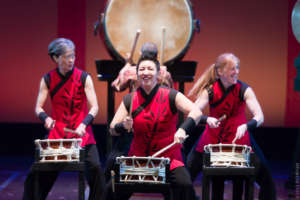 3 Taiko performers playing small drums, wearing vivid red & black, large drum in background